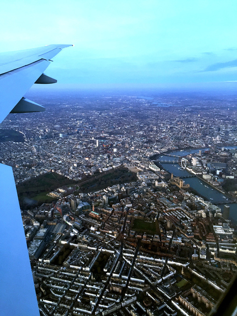 An aerial birds eye view of London - Flying with Qatar Airways past the River Thames, the London Eye, Big Ben, Houses of Parliament, Westminster Abbey and Buckingham Palace - Tily Travels.
