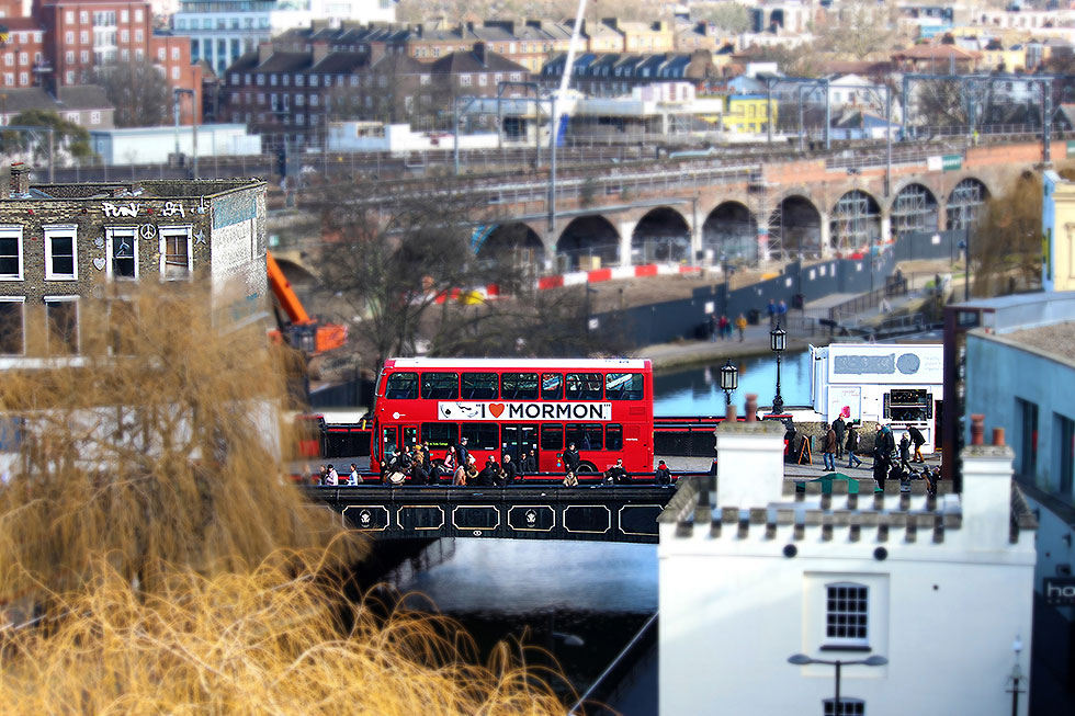 A red double decker bus on Camden High Street, crossing Camden Lock, with the now demolished and soon to be redeveloped Camden Lock Village in the background - Camden Town, London England - Tily Travels.