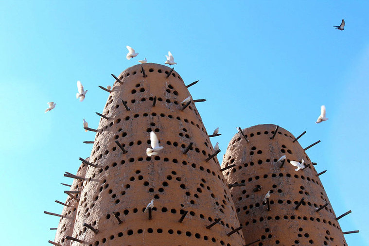 Qatar Airways free Doha city tour - Katara Cultural Village dovecote with doves in flight.
