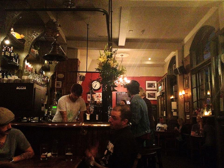 The dimly lit main bar at the Hawley Arms - Camden Town, London England - Tily Travels.