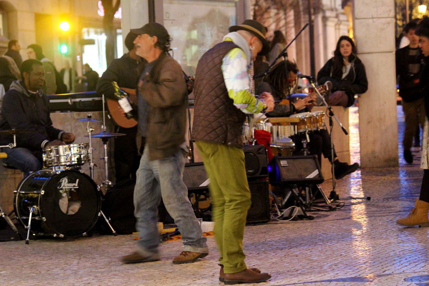 Musicians and street performers busking while people dance to the music outside of Café a Brasileira on Rua Garrett, Lisbon at night, Portugal.