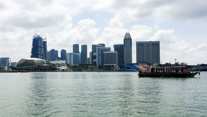Singapore skyline and a bumboat cruising down the Singapore river - Singapore River Cruise.