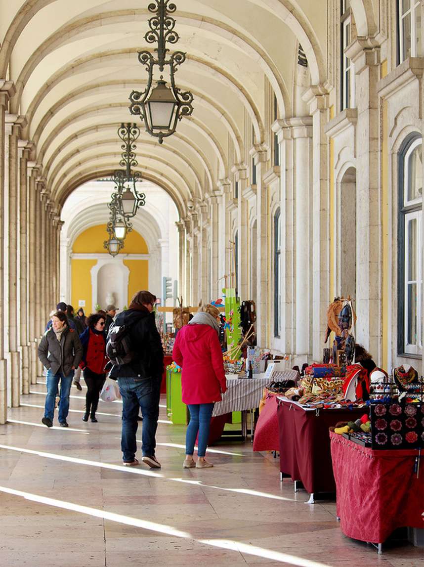 Shopping at the handicraft market under Praca do Comercio's arcades. Lisbon, Portugal.
