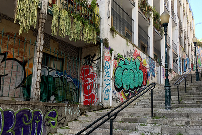 Graffiti covered homes and stairway on Calcada do Lavra, Lisbon, Portugal - Calçada do Lavra street art.