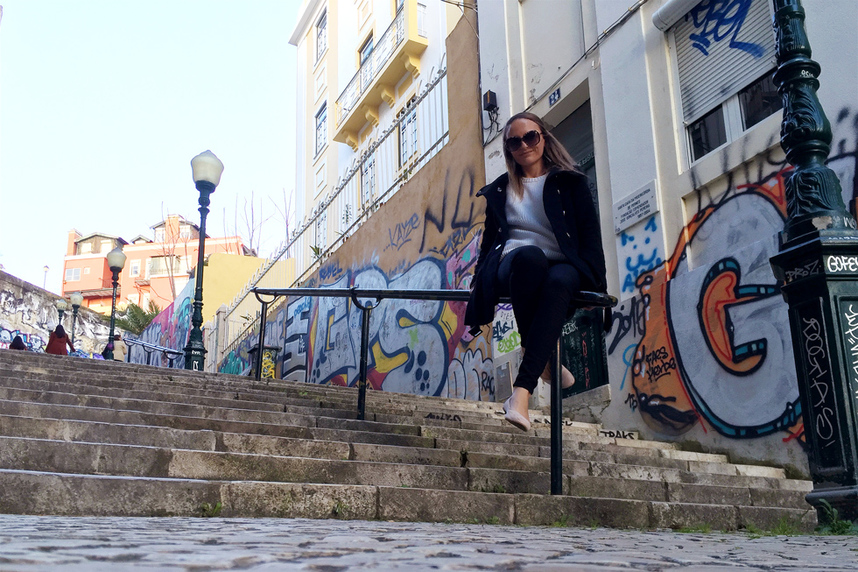 Sitting in front of colourful street art and graffiti on the Calcada do Lavra stairs, Lisbon, Portugal - Calçada do Lavra street art.