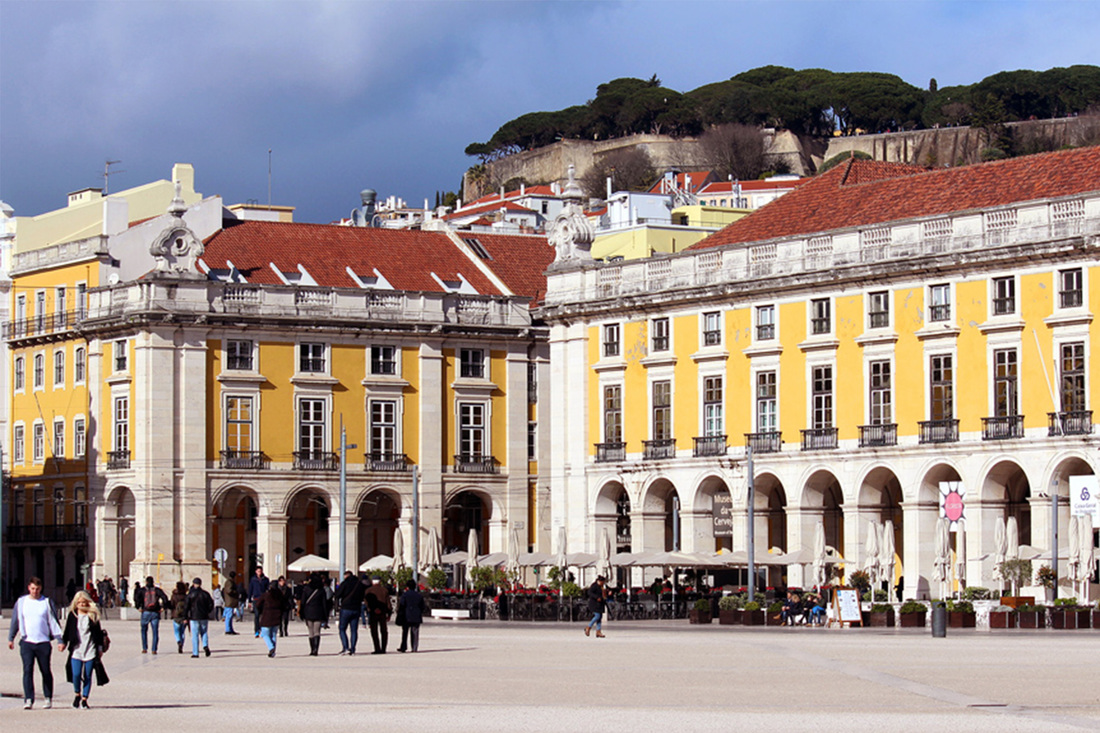 Traditional Portuguese yellow painted buildings in Praça do Comércio, overlooked by São Jorge Castle/ Castelo de São Jorge - Pombaline-Baixa, Lisbon - Portugal.