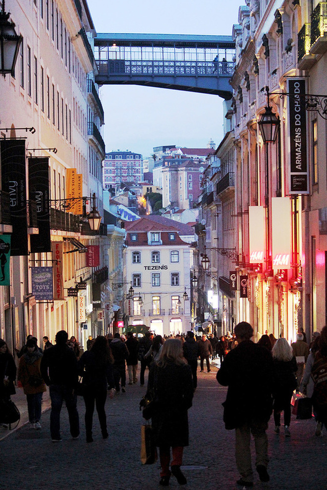 People shopping in the busy Baixa-Chiado district at dusk - Lisbon - Portugal.