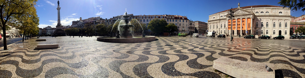Panorama of Rossio Square (Pedro IV Square) - Column of Pedro IV, fountain, patterned pavement and the National Theatre D.Maria II - Pombaline-Baixa, Lisbon - Portugal.