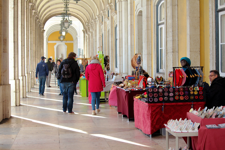 People shopping at the Praça do Comércio handicrafts market under the plaza's north arcades - Praça do Comércio - Pombaline-Baixa, Lisbon - Portugal.