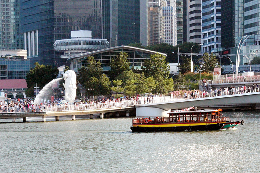 An historic bumboat cruising past Merlion Park, Singapore.