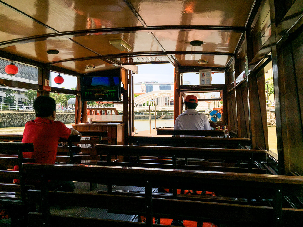 The interior of the historic bumboat with the tour guide and driver - Singapore River Cruise.
