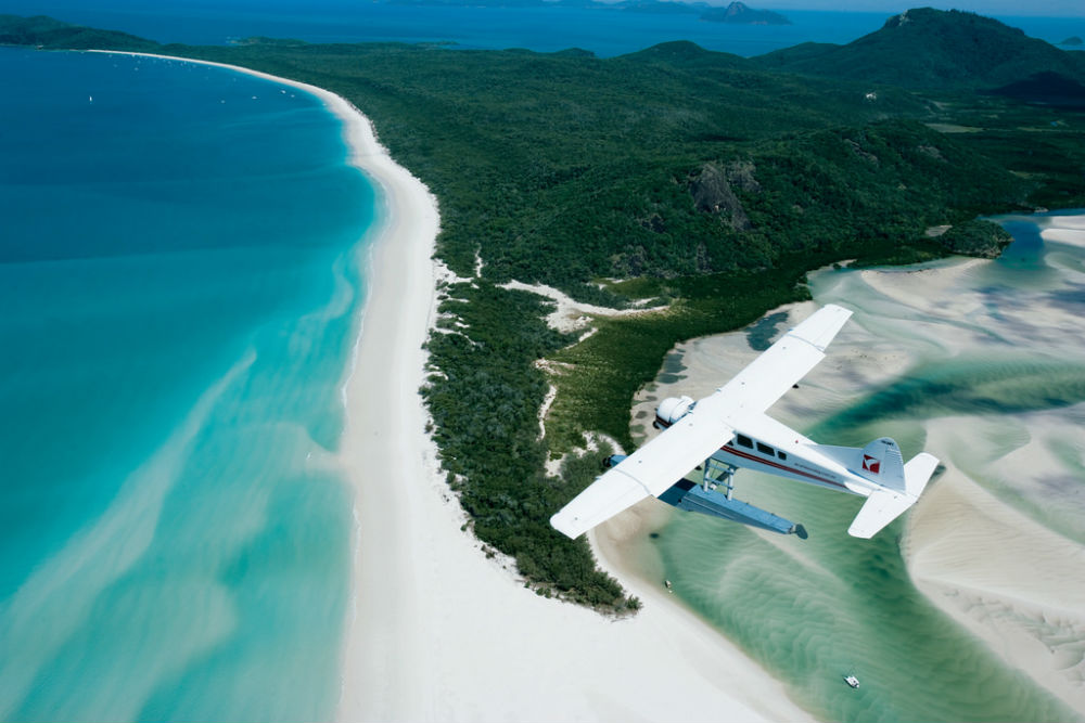 4 Incredible Islands to Visit in Australia - A seaplane flying over Whitehaven Beach, Whitsunday Islands, Queensland, Australia.